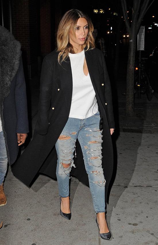 استفاده از کت مشکی بلند توسط کیم کارداشیان روی لباس سفید و شلوار جین زاپ دار و کفش پاشنه بلند