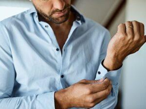 پیراهن آبی که شخص در حال بستن دکمه سراستین آن است - مجله اینترنتی مد سارابارا