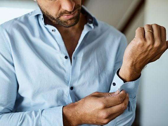 پیراهن آبی که شخص در حال بستن دکمه سراستین آن است - مجله مد و فشن سارابارا