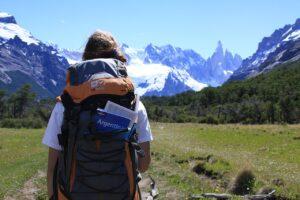 یک بک پکر حرفه ای در مسیر ورود به جنگل سر سبز و کوهستان برفی با کوله پشتی حرفه ای و نقشه و کتاب های مسافرتی