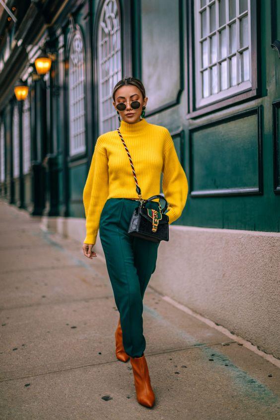 شلوار سبز تیره و پلیور زرد رنگ چکمه قهوهای زن جوان