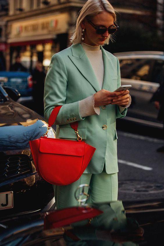 کت و شلوار سبز پاستلی زن با موهای روشن عینک دودی و کیف قرمز