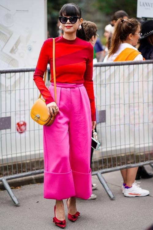شلوار صورتی رنگ و بلوز قرمز به همراه کیف خردلی و گوشوارههای مروارید شکل