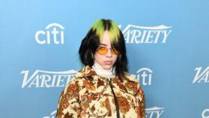 استایل منحصر به فرد بیلی آیلیش شامل موهای سبز و مشکی و لباس طرحدار با بک آبی و عینک